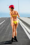 Woman in swimsuit with rollers on the highway Royalty Free Stock Photography