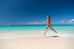 Woman in swimsuit running on sea beach. With white sand, turquoise water and blue sky on sunny day on natural environment. Sun tanning, bathing. Summer vacation Stock Image