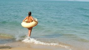 Woman in Swimsuit On Sandy Shore on Sea Background
