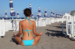 Woman in swimsuit seats on beach. Stock Image