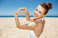 Woman in swimsuit showing heart shaped hands at sandy beach Stock Photo