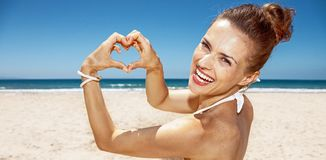 Woman in swimsuit showing heart shaped hands at sandy beach Stock Photography