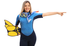 Woman in a swimsuit and snorkeling equipment pointing right Royalty Free Stock Photo
