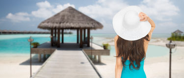 Woman in swimsuit and sun hat from back on beach. People, summer holidays, travel, tourism and vacation concept - woman in swimsuit and sun hat from back over Royalty Free Stock Photography