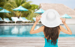 Woman in swimsuit and sun hat from back over beach. People, summer holidays, travel, tourism and vacation concept - woman in swimsuit and sun hat from back over Royalty Free Stock Photo