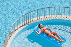 Woman in swimsuit sunbathes lying on inflatable mattress Stock Image
