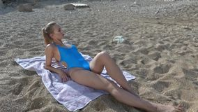 Woman sunbathing on beach stock video