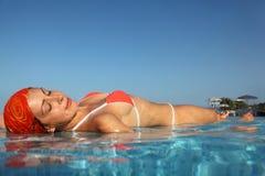 Woman in swimsuit sunbathing in water in pool Stock Images