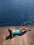 Woman In Swimsuit Sunbathing On Yacht's Floorboard Royalty Free Stock Photo