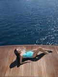Woman In Swimsuit Sunbathing On Yacht's Floorboard. High angle view of woman in swimsuit sunbathing on yacht's floorboard Royalty Free Stock Photo