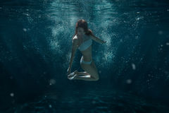 Woman in swimsuit swims under water. Woman in swimsuit swims under water among the light rays Stock Images