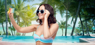 Woman in swimsuit taking selfie with smatphone Royalty Free Stock Images