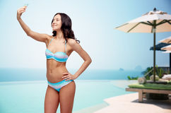 Woman in swimsuit taking selfie with smatphone Stock Images