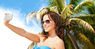 Woman in swimsuit taking selfie with smatphone Royalty Free Stock Image