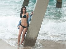 Woman in a swimsuit under the pier Royalty Free Stock Image