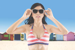 Woman in swimsuit wears sunglasses at coast Stock Images