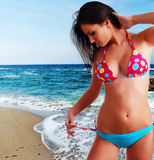 Woman in swimwear and beach. Beautiful young woman in bright swimwear at the beach Stock Photos