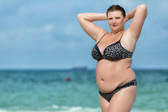 Woman in swimwear at the sea. Overweight young woman in swimsuit posing against horizon over water. Female with arms raised corrects her hair looking at camera Stock Photography