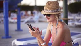 Woman in swimwear sitting by swimming pool surfing on smart phone. Woman in swimwear, straw hat and sunglasses sitting by swimming pool using surfing on smart stock video footage