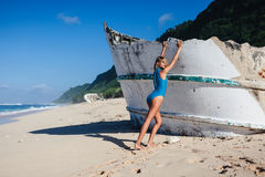 Woman in swimwear walking on sandy beach during daytime near broken ship. Young attractive woman in swimwear walking on sandy beach during daytime near broken Stock Photography