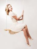Woman on a swing. Beautiful young blond woman on a swing against light studio background Stock Photo