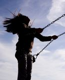 Woman on a swing. A woman swings high on a swing Stock Photos