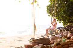 Woman on swing at beach. Young woman on swing on beach at sunrise Stock Images