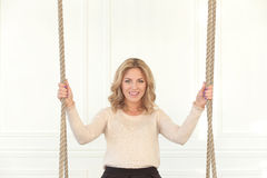Woman on the swing. Blonde girl with curly hair sitting on the swing stock photos