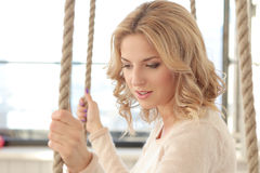 Woman on the swing. Blonde girl with curly hair sitting on the swing stock photo