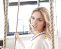 Woman on the swing. Blonde girl with curly hair sitting on the swing royalty free stock photography