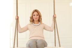 Woman on the swing. Blonde girl with curly hair sitting on the swing royalty free stock images