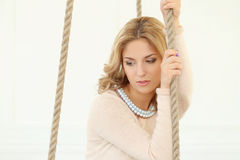 Woman on the swing. Blonde girl with curly hair sitting on the swing stock images