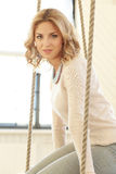 Woman on the swing. Blonde girl with curly hair sitting on the swing royalty free stock photos