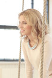 Woman on the swing. Blonde girl with curly hair sitting on the swing royalty free stock photo