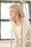 Woman on the swing. Blonde girl with curly hair sitting on the swing stock image