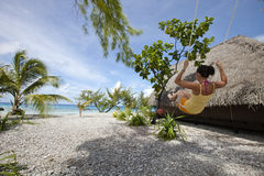 Woman on swing front of blue lagoon royalty free stock photos