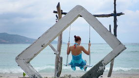 Woman on a swing in Gili Air island, Indonesia. Idyllic scene of a girl in turquoise sarong gently swinging on a rustic, seaside swing. Gili Air island stock video footage