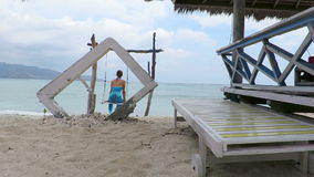 Woman on a swing in Gili Air island, Indonesia. Woman swinging on idyllic seaside swing, made out of driftwood. Gili Air, Indonesia stock video footage