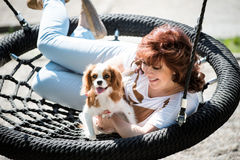 Woman swing with her dog Stock Photos
