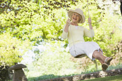 Woman in a swing outdoors smiling Stock Images