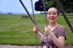 Woman on Swing with Surprise Expression. A very happy young woman shows a surprised expression Royalty Free Stock Images