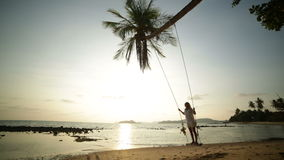 Woman on a swing in tropical settings stock video footage