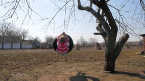 A woman on a swing. In the village stock video