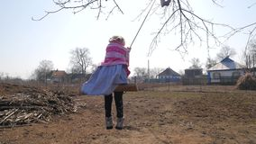 A woman on a swing. In the village stock video footage