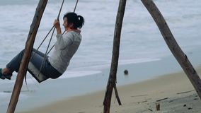 Woman on a swing. Woman swinging on a swing at tropical beach during stormy weather. Slow motion people footage stock video