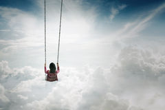 Woman swinging above the clouds Stock Photography