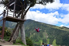 Woman swinging in the end-of-the-world swing in the town of Banos, Ecuador. The small town of Banos or Baños, in Ecuador, is famous for it`s tree house and stock images