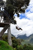 Woman swinging in the end-of-the-world swing in the town of Banos, Ecuador. The small town of Banos or Baños, in Ecuador, is famous for it`s tree house and the royalty free stock photo