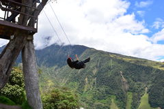 Woman swinging in the end-of-the-world swing in the town of Banos, Ecuador. The small town of Banos or Baños, in Ecuador, is famous for it`s tree house and stock photo