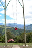 Woman swinging in the end-of-the-world swing in the town of Banos, Ecuador. The small town of Banos or Baños, in Ecuador, is famous for it`s tree house and the stock photo